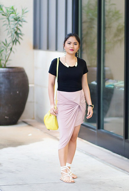 With black t shirt, pale pink wrap skirt and yellow bag