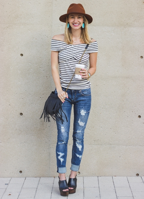 With brown hat, crossbody fringe bag, distressed jeans and black shoes