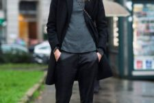 With gray shirt, printed slip on shoes, black coat and bag