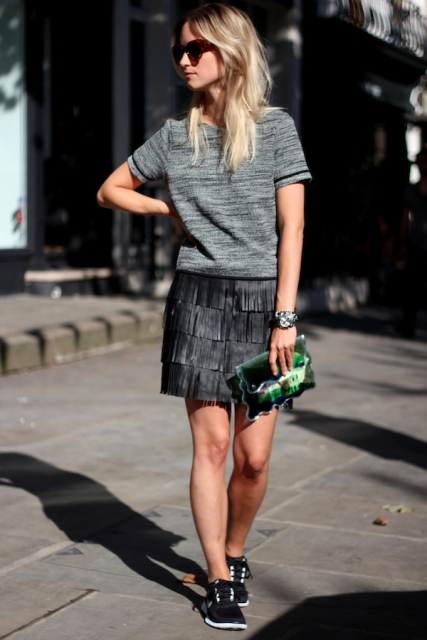 With gray shirt, sneakers and green clutch