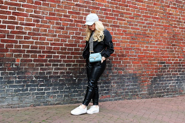 With gray shirt, white sneakers, light blue cap and blue bag