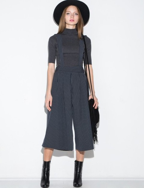 With gray turtleneck, black hat, black ankle boots and fringe bag
