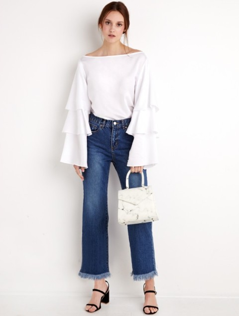 With high-waisted jeans, white bag and black sandals