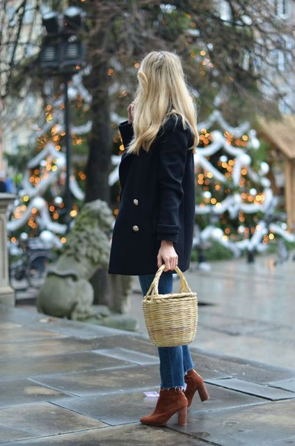 With navy blue jacket, jeans and brown boots