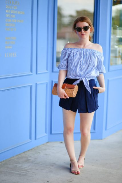 With navy blue shorts, flat sandals and clutch