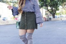 With olive green mini skirt, gray over the knee boots and printed bag