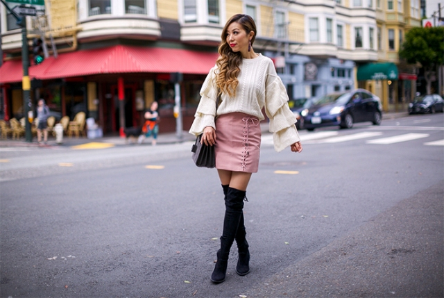 With pale pink skirt, black over the knee boots and leather bag