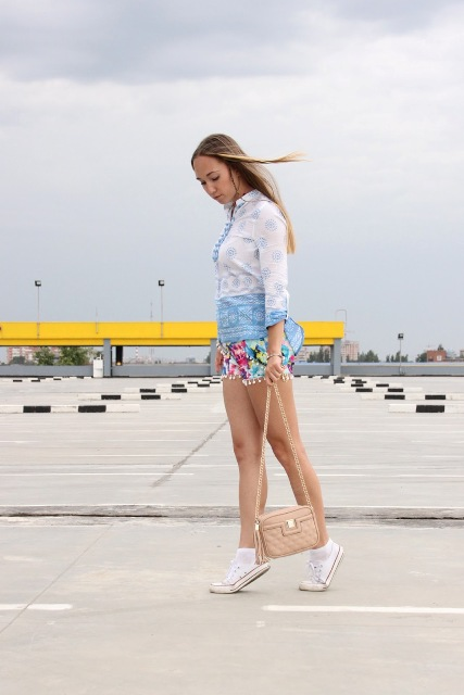 With printed shirt, white sneakers and beige bag