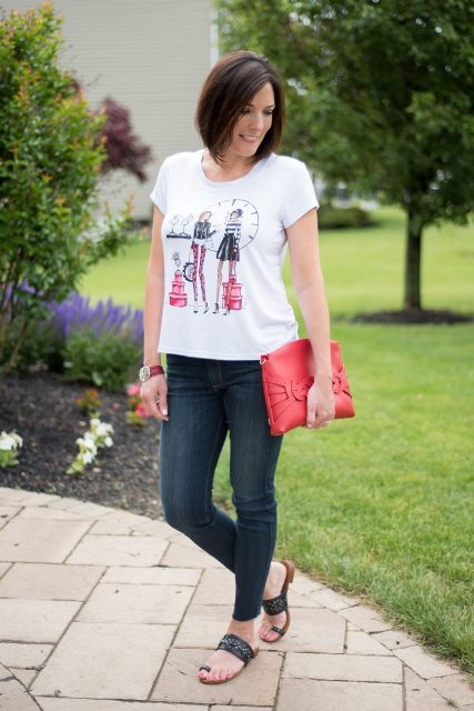 With printed t-shirt, skinny jeans and red clutch