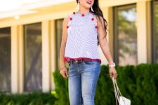 With printed top, distressed jeans and white bag