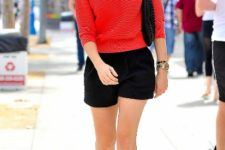 With red sweatshirt, black shorts and bag
