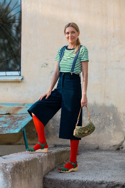 With striped shirt, red socks, green sandals and printed small bag