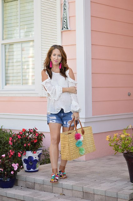 With white off the shoulder blouse, denim shorts and straw tote