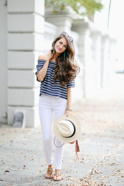 With white pants, white and black hat and flat sandals