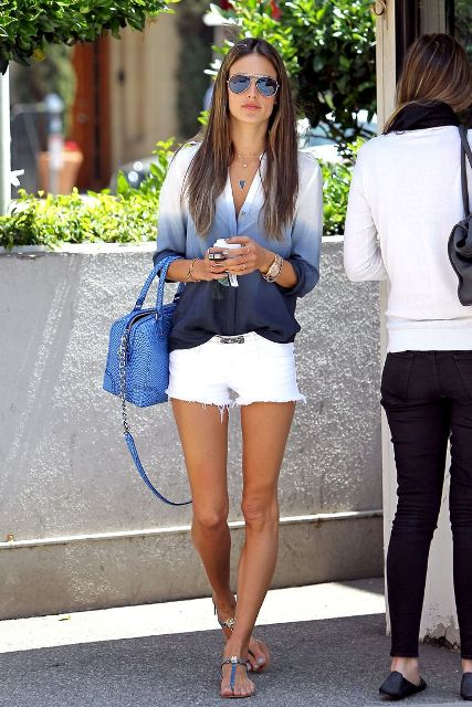 With white shorts, flat sandals and blue bag