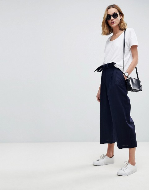 With white t shirt, white sneakers and black mini bag