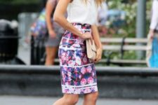 With white top, floral knee-length skirt and beige clutch