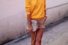 With yellow sweatshirt, beige shorts and beige clutch