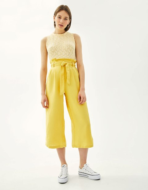 With yellow top and sneakers