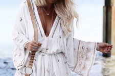 02 a boho white beach romper with lace detailing and embroidery plus a plunging neckline