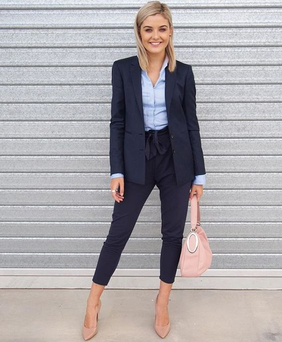 a navy suit with cropped pants, a blue shirt, nude heels and a blush bag
