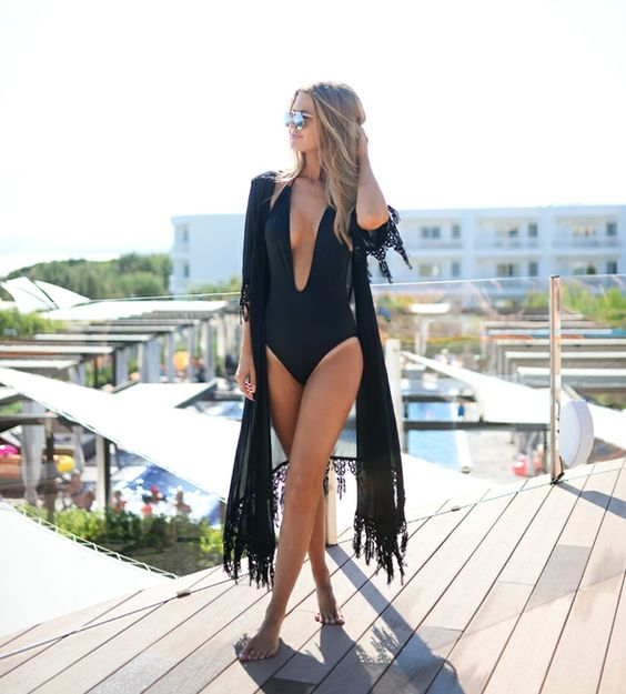 a modern black one-piece swimsuit with a plunging neckline is a bold and sexy idea