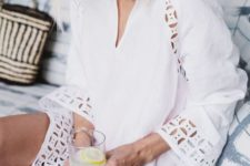 03 a white tunic with a V-neckline and perforations on the edges looks very boho-like