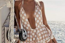 04 a blush swimsuit with a peplem detail, pompoms, polka dots and a plunging neckline