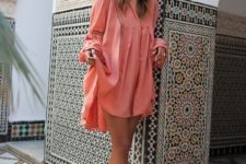 04 a coral mini dress with long sleeves and decorative holes looks very tropical-like