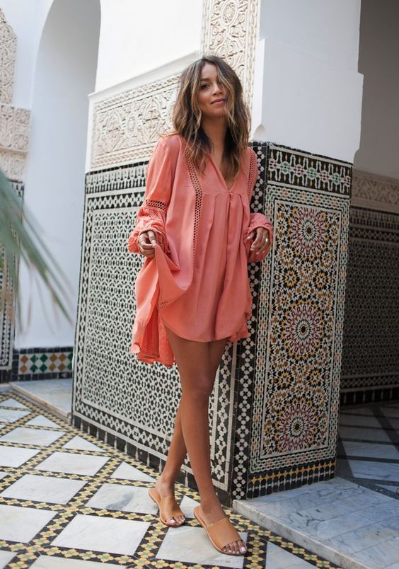 a coral mini dress with long sleeves and decorative holes looks very tropical like