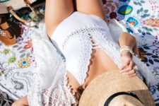 04 a white one piece swimsuit wih a crocheted lace trim and a plunging neckline for a boho look