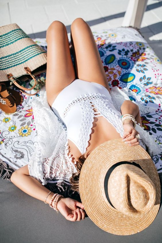 a white one piece swimsuit wih a crocheted lace trim and a plunging neckline for a boho look
