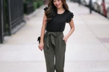 05 a black top with ruffled sleeves, olive green pants with a bow tie, nude shoes and a black bag