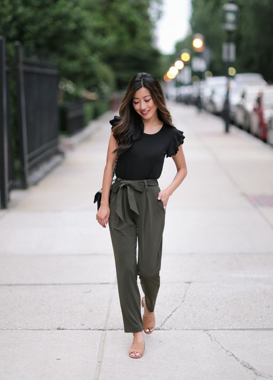 a black top with ruffled sleeves, olive green pants with a bow tie, nude shoes and a black bag