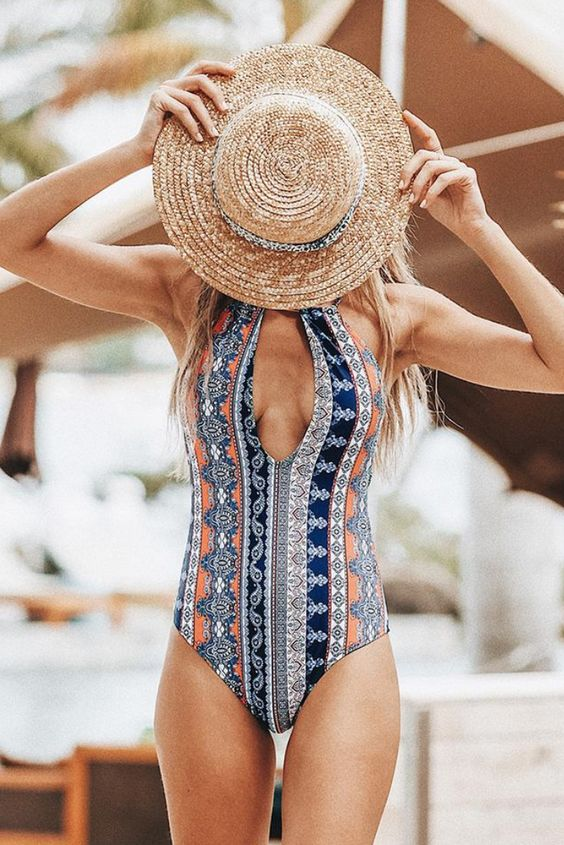 a colorful printed one piece swimsuit with a halter plunging neckline for a boho look