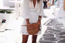 06 a white mini dress with a plunging neckline, long sleeves and lace, tan shoes and a bag plus a floppy hat