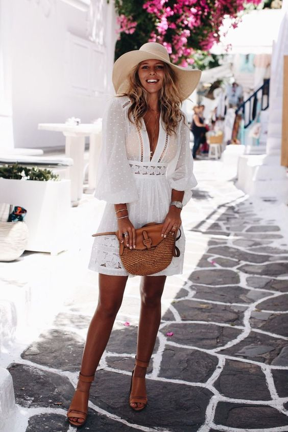 a white mini dress with a plunging neckline, long sleeves and lace, tan shoes and a bag plus a floppy hat