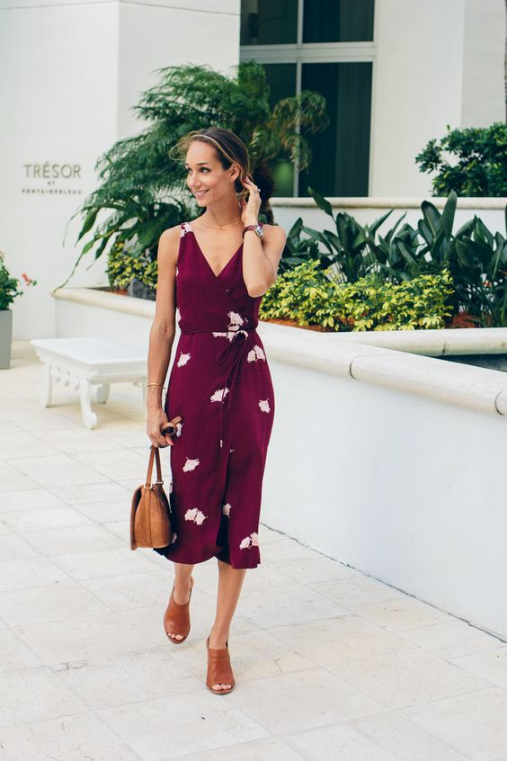 a burgundy midi wrap dress with a V-neckline, tan shoes and a tan bag