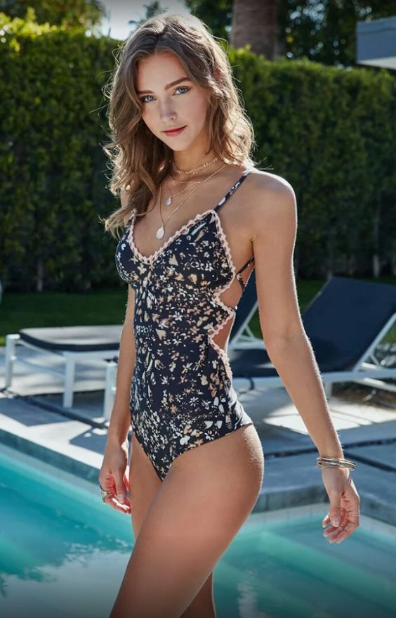 a navy one piece floral swimsuit with spaghetti straps and a strappy back with a lace trim