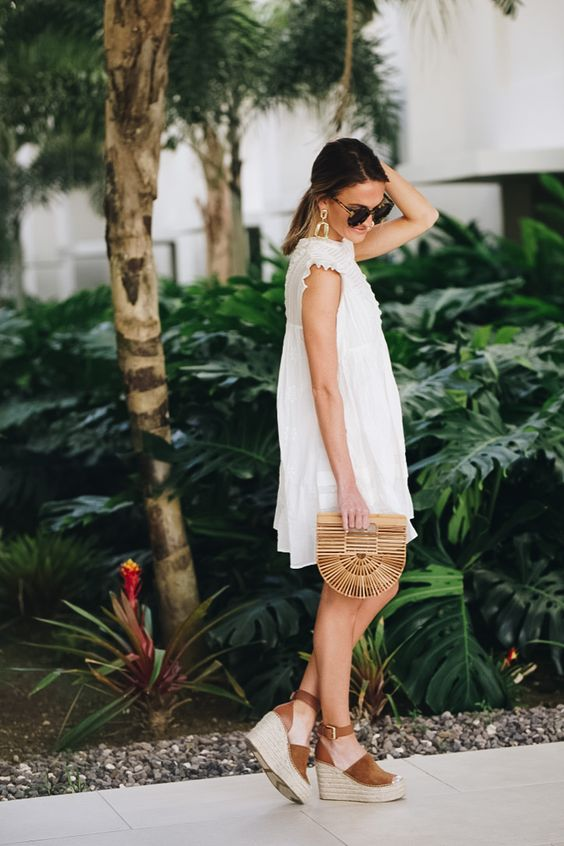 a short white dress with lace detailing, wedges and a wooden clutch