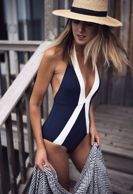 a navy and white halter neckline geometric swimsuit with a plunging neckline and stripes for a wow effect