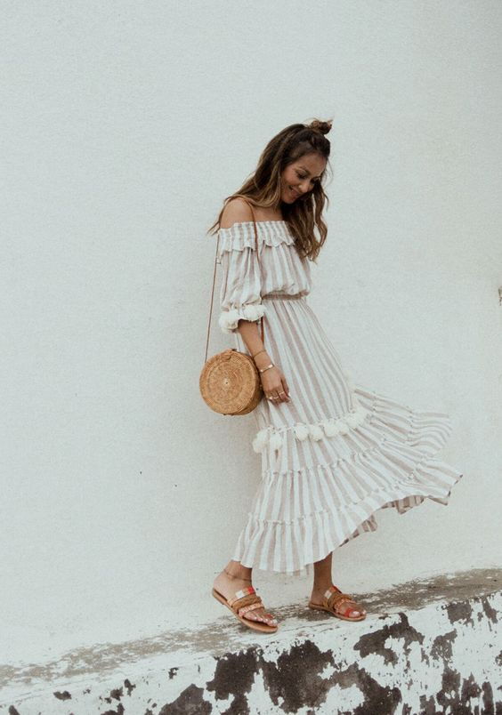 a comfy light-colored striped off the shoulder long sleeve midi dress, colorful sandals and a round straw bag