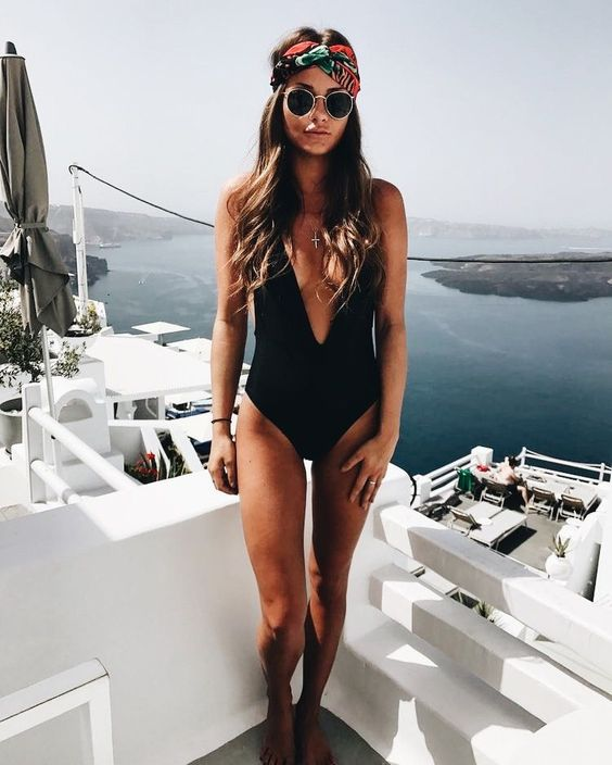 a black one piece swimsuit with a deep plunging neckline is a trendy and sexy look