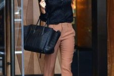 11 salmon pink cropped pants, a black shirt, black heels and a large bag