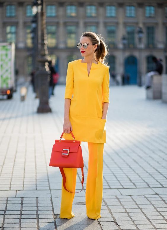 a bright yellow pantsuit with a long pocket top and a hot red bag for an office look
