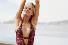 12 a burgundy floral one piece swimsuit with a plunging neckline and a strap to make it more modest
