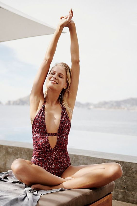 a burgundy floral one piece swimsuit with a plunging neckline and a strap to make it more modest