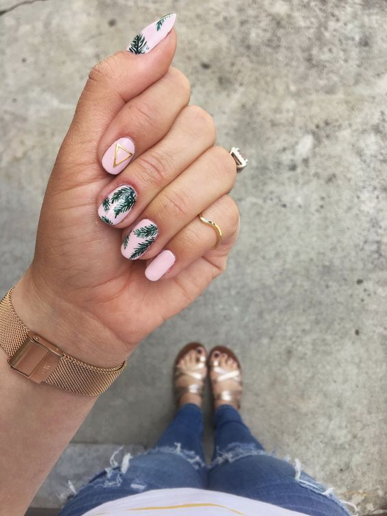 a pink manicure with tropical leaf prints and geometric touches