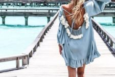 13 a powder blue tunic with bell sleeves, a cutout back with lacing and multiple tassels