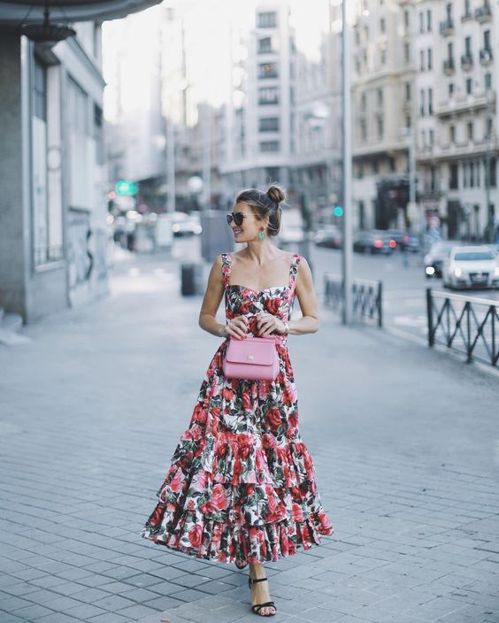 a thick strap bright floral maxi dress with a ruffled skirt, a pink bag and black shoes